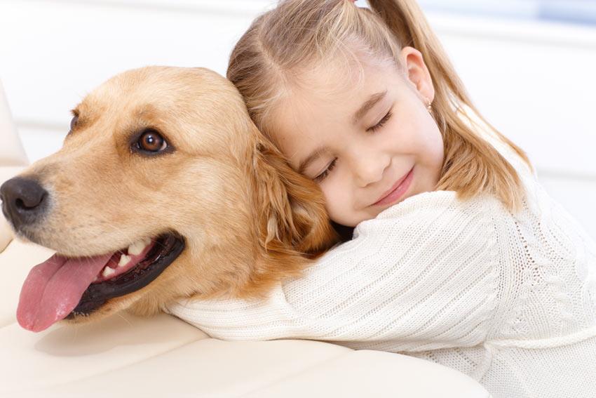 Ein kleines Mädchen umarmt ihren Golden Retriever